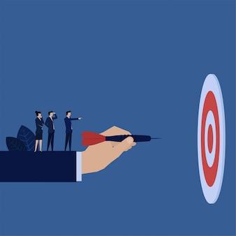 La main de l'entreprise tient la fléchette et le gestionnaire demande de viser la métaphore de la cible.