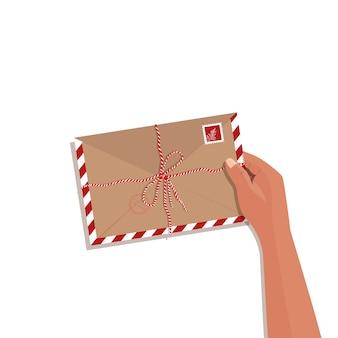 Main avec enveloppe isolée. colis fermé dessiné à la main avec lettre