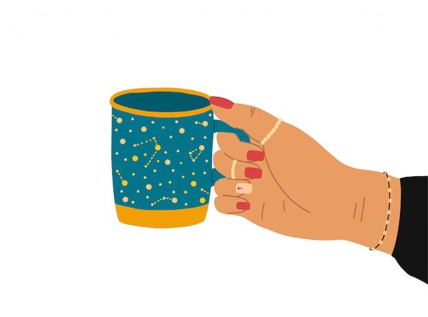 Une main féminine avec une belle manucure, des bijoux et une horloge tient une tasse de thé.