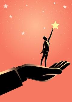 Main géante aidant une femme d'affaires à tendre la main aux étoiles