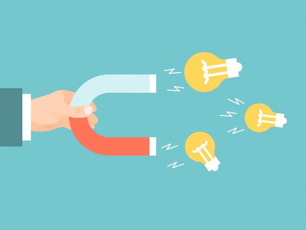 La main d'homme d'affaires avec aimant attire les ampoules. ampoule magnétique à idées attractives.