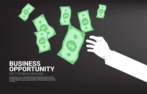 Main d'homme d'affaires essaie de récupérer de l'argent qui tombe du ciel. concept d'opportunité d'affaires et d'économie