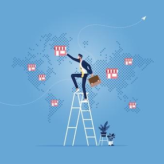Main d'homme d'affaires mis magasin de franchise sur la carte du monde, concept d'entreprise de franchise