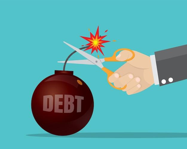 Main d'homme d'affaires tenant des ciseaux pour couper la bombe de la dette.