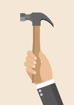 Main d'homme d'affaires tenant un marteau.