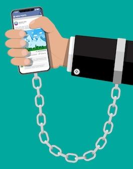 La main de l'homme enchaînée et enchaînée au téléphone mobile intelligent. dépendance du gadget avec les médias sociaux. accro aux réseaux sociaux, au chat et à la messagerie.