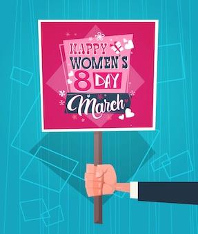 Main d'homme tenant la bannière avec la journée de la femme heureuse saluant abstrait style rétro bleu