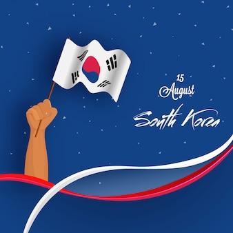 Main de l'homme tenant le drapeau national du fond de la corée du sud