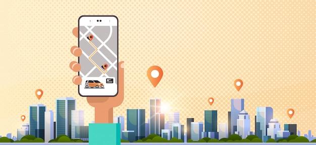 Main humaine à l'aide de la commande en ligne de partage de voiture de taxi, application mobile, concept de transport, service d'autopartage, écran de smartphone avec carte gps, paysage urbain moderne