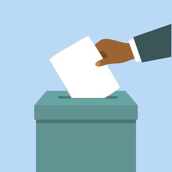 Main noire mettant un vote dans la boîte