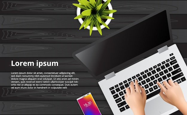 Main en tapant portable sur le bureau en bois avec illustration de téléphone, plante.