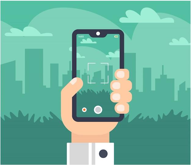 Une main avec un téléphone prend des photos de la ville