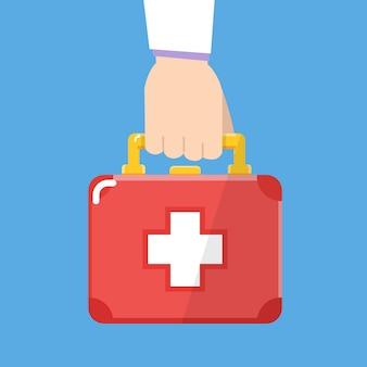 Main tenant la boîte de trousse de premiers soins. design plat. illustration vectorielle.