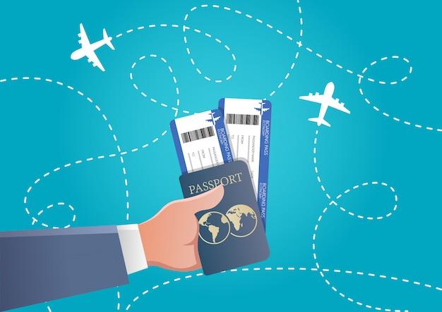 Main tenant la carte d'embarquement et passeport en fond bleu