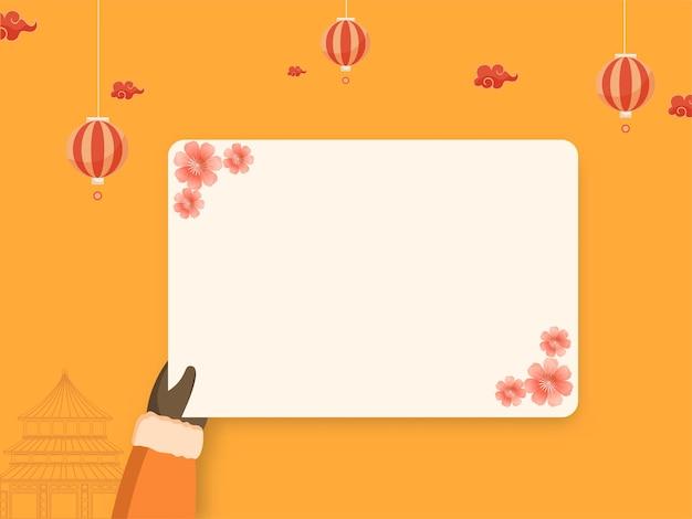 Main tenant une carte de voeux vide avec des fleurs de sakura