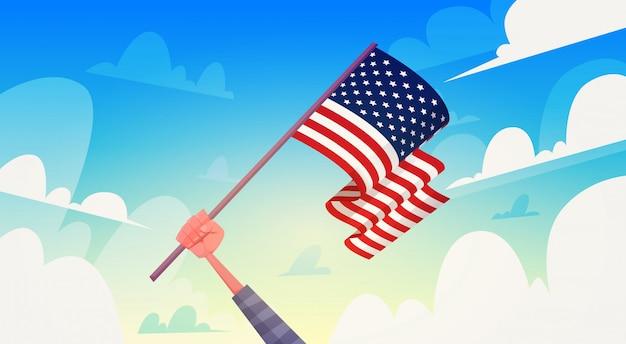 Main tenant le drapeau des états-unis au cours de la journée nationale des patriotes de ciel bleu