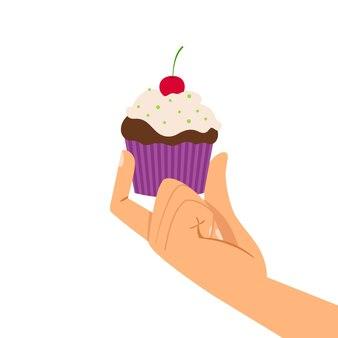Main tenant un petit gâteau aux cerises