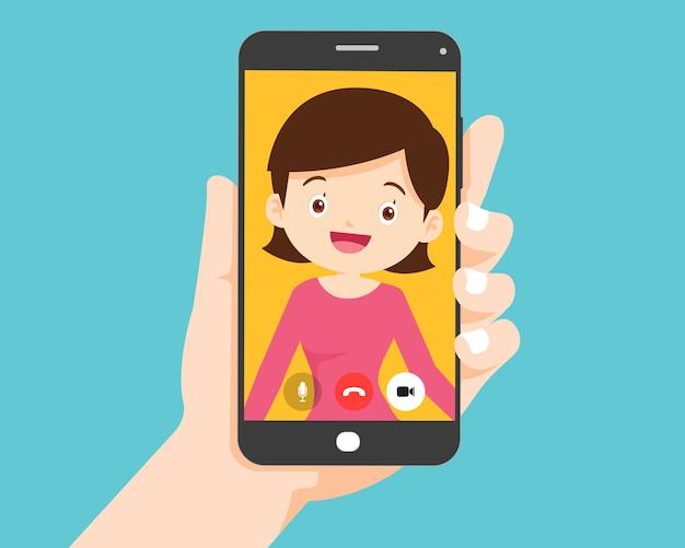 Main tenant un smartphone avec une femme intelligente à l'écran. appel vidéo avec une jeune femme