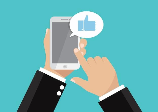 Main tenant le smartphone avec l'icône thumbs up sur l'écran.