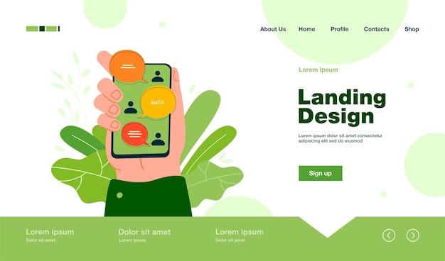 Main tenant un smartphone avec interface de discussion en ligne, messages envoyés et reçus sur la page de destination à l'écran dans un style plat