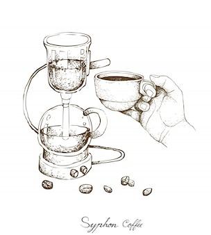 Main tenant une tasse de café avec une cafetière à siphon