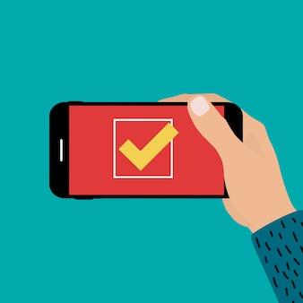 Main tenant le téléphone mobile avec signe de marque oui.