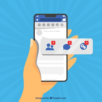 Main tenant le téléphone avec des notifications facebook