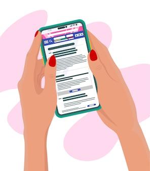 Main tenir le téléphone portable lecture de nouvelles