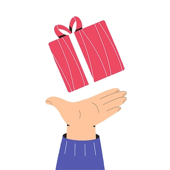 La main tient une boîte-cadeau de noël salutations de vacances donne des cadeaux