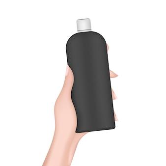 La main tient une bouteille en plastique noire. main féminine réaliste avec une bouteille. bon pour le shampooing ou le gel douche. isolé. vecteur.