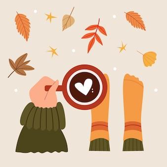 La main tient un café parfumé avec un coeur vue de dessus les feuilles d'automne tombent ambiance festive