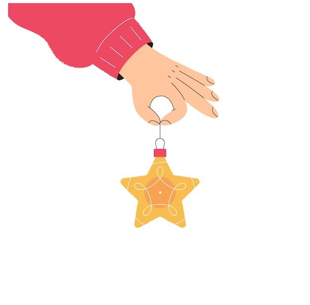La main tient une décoration d'arbre de noël d'étoile de jouet de noël