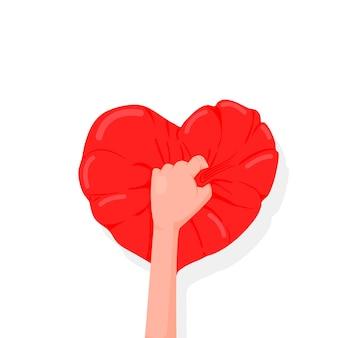 Main tient un oreiller en forme de coeur, un cadeau pour la saint-valentin.