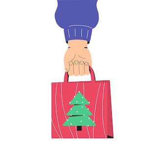 La main tient un paquet de cadeau de noël achats de noël salutations de vacances