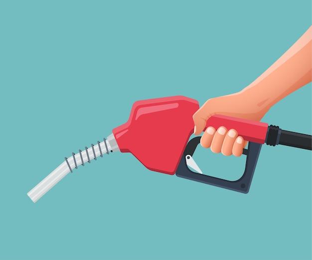 La main tient la pompe à buse de carburant.