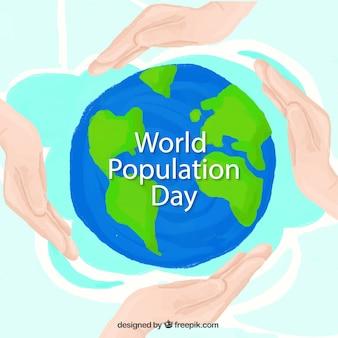 Les mains avec de l'arrière-plan du monde de la journée de la population