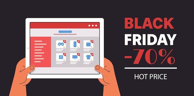 Mains choisissant des produits sur l'écran de la tablette distributeurs en gros en ligne, vente de vendredi noir