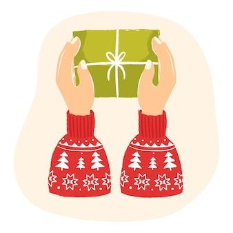 Mains dans un chandail tenant un cadeau de noël échange de cadeaux de noël carte de nouvel an le lendemain de noël