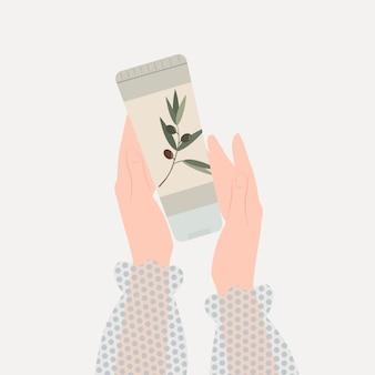 Les mains des femmes tiennent un tube de crème d'olive crème pour le visage et le corps concept de soins de la peau et de cosmétiques