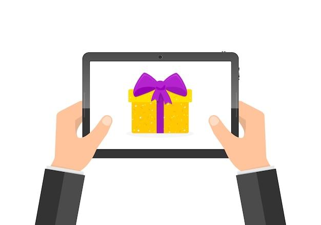 Mains d'homme d'affaires avec tablette et boîte-cadeau sur l'écran
