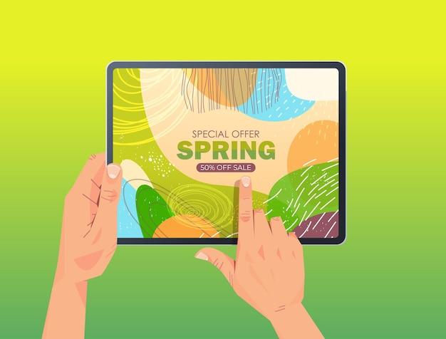 Mains humaines à l'aide de tablet pc avec flyer bannière de vente de printemps ou carte de voeux sur illustration horizontale de l'écran