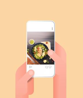 Mains humaines en utilisant une application mobile en ligne plat de salade fraîche préparé pour blog sur écran de smartphone blogging alimentaire réseau de médias sociaux concept food hunter review vertical