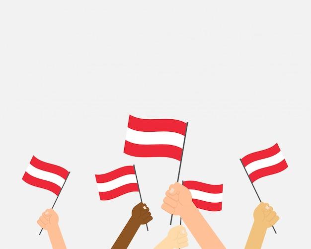 Mains d'illustration vectorielle tenant des drapeaux de l'autriche