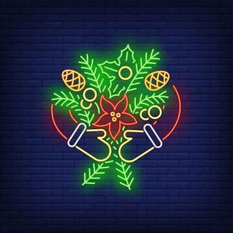 Mains en mitaines embrassant des brindilles de sapin avec des cônes dans un style néon