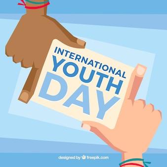 Mains avec note de la journée internationale de la jeunesse