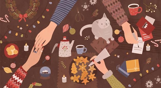 Mains de personnes assises autour d'une table et se préparant pour noël - faire des décorations festives, écrire sur des cartes de voeux, décorer des biscuits. vue de dessus. illustration vectorielle de dessin animé coloré vacances.