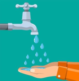 Les mains sous l'eau qui tombe du robinet
