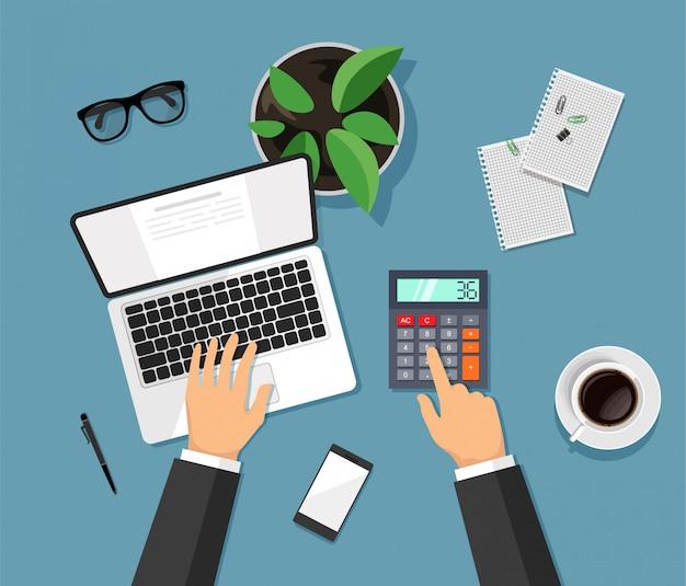 Les mains tapent sur un ordinateur et comptent sur une calculatrice. dessus de bureau de travail moderne dans un style branché.
