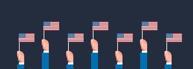 Mains tenant la bannière de drapeaux américains