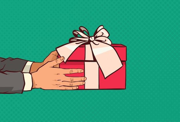 Mains tenant une boîte cadeau rouge avec un arc présent pour les fêtes sur pop art comique